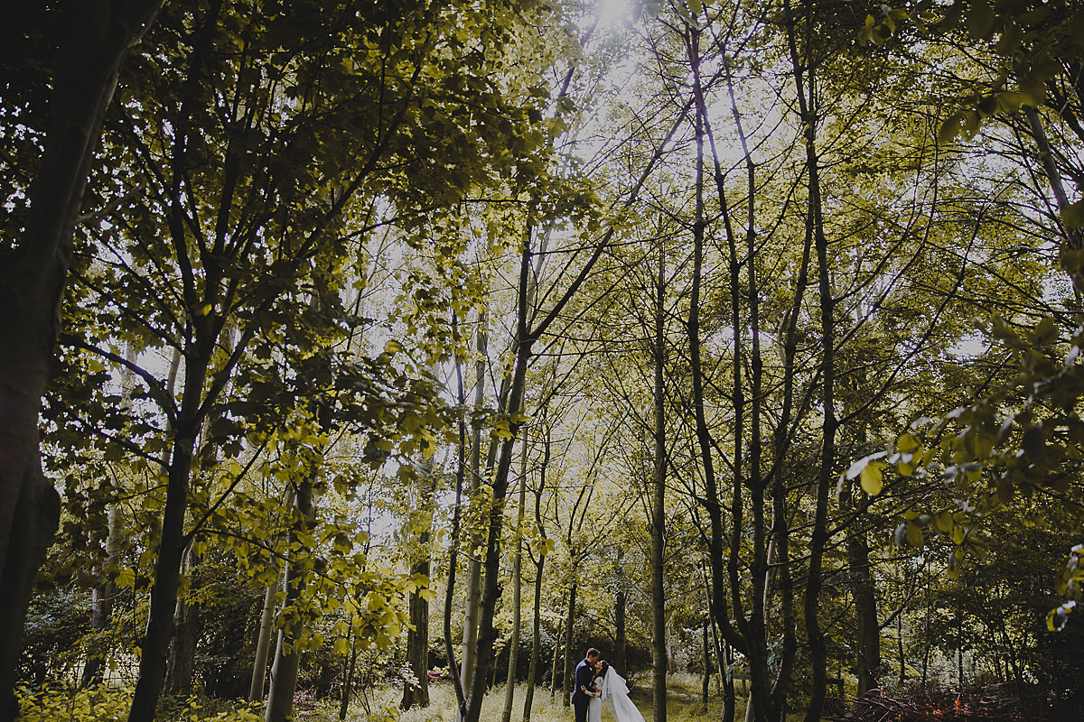 hengrave hall wedding photo - bride and groom sharing a moment in the woods